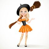 Cute teenage witch in orange dress with a broom on her shoulder Stock Photos
