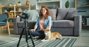 Cute teenager blogger recording videoblog sitting on floor at home with pet dog. Cute teenager popular blogger is recording videoblog sitting on floor at home stock video
