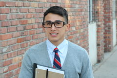 Cute teenager boy in formal high school uniform and glasses smiling Stock Photo