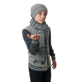 Cute teenager boy in gray sweater over white isolated background. Cute teenager boy in gray sweater, hat and scarf holding something over white isolated Stock Photo
