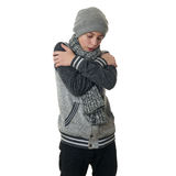 Cute teenager boy in gray sweater over white isolated background. Cute teenager boy in gray sweater, hat and scarf trying get warmer with crossed arms over white Royalty Free Stock Photography