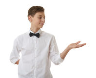 Cute teenager boy over white  background. Cute teenager boy in white shirt and black bow tie holding something on palm over white  background, half body Stock Images