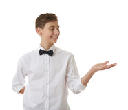 Cute teenager boy over white isolated background. Cute teenager boy in white shirt and black bow tie holding something on palm over white isolated background Royalty Free Stock Photo