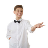 Cute teenager boy over white isolated background. Cute teenager boy in white shirt and black bow tie holding something on palm over white isolated background Royalty Free Stock Images