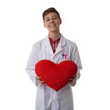 Cute teenager boy over white isolated background. Cute teenager boy wearing white lab medic coat with red plush heart over white isolated background as science Stock Image
