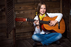 Cute teenager cowgirl plays the guitar. Cute teenager cowgirl on a ranch and plays the guitar Royalty Free Stock Photo