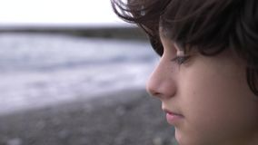 A cute teenager with curly hair against the backdrop of the sea. 4k, slow motion stock video