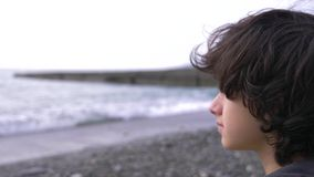 A cute teenager with curly hair against the backdrop of the sea. 4k, slow motion stock footage