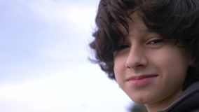 Cute teenager with curly hair against the blue sky 4k, slow-motion shooting stock footage