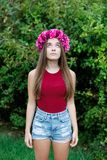 Cute teenager girl with a beautiful wreath on her head. Cute teenager girl in a park with a beautiful wreath on her head Royalty Free Stock Photography