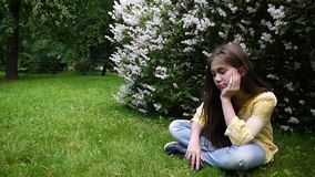 Cute teenager girl checking phone and waiting phone call sitting in park. Video footage HD shooting static camera. Cute teenager girl checking cellphone and stock video