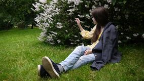 Cute teenager girl checking phone and waiting phone call sitting in park. Video footage HD shooting static camera. Cute teenager girl checking cellphone and stock video footage