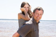 Teenager girl daughter make father handsome piggyback on sunny day at ocean sea beach. Cute teenager girl daughter make father handsome piggyback on sunny day at Royalty Free Stock Photos