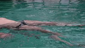 Cute teenager girl playing laughing swimming in hotels pool having fun.  stock video footage