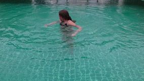 Cute teenager girl playing laughing swimming in hotels pool having fun.  stock footage
