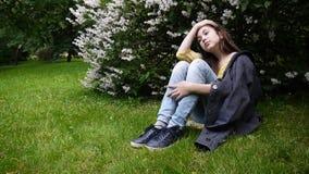 Cute teenager girl sitting in park. Hd video footage static camera. Cute teenager girl sitting in park. Hd video stock footage