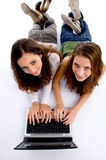 Cute teenager girls busy on laptop Stock Photo