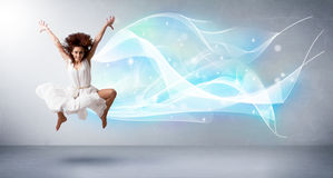 Cute teenager jumping with abstract blue scarf around her Stock Photography