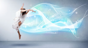 Cute teenager jumping with abstract blue scarf around her Royalty Free Stock Photography