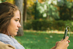 Cute Teenager Listening to Music on a Cell Phone Royalty Free Stock Photo