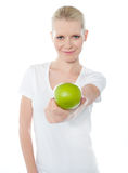 Cute teenager offering green apple. Dressed in white top Stock Photography