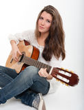 Cute teenager playing the guitar Royalty Free Stock Images