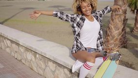 Cute teenager sitting on ledge with skateboard stock video footage