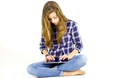 Cute teenager using tablet looking camera isolated Royalty Free Stock Photos