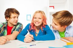 Cute teens girl and boys do homework project. Three cute kids boys and beautiful young teen girl smiling doing homework writing in textbook Royalty Free Stock Photos