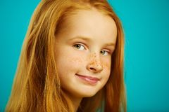 Cute ten year old redheaded girl on blue isolated background, close-up shot of beautiful child with freckles. royalty free stock photos