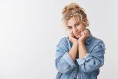 Cute tender feminine delightful pretty blond curly-haired scandinavian woman blue eyes gazing flirty camera tilt head. Lean face palms flirting, romantic eye royalty free stock image