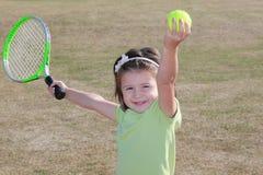 Cute tennis lerner. Little girl practicing tennis serve Stock Photo