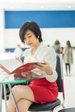 Cute Thai (Asian) businesswoman is reading her document file in Royalty Free Stock Photos