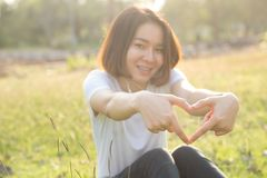 Cute Thai asian girl love heart shape with her hands. In sunshine Royalty Free Stock Photography