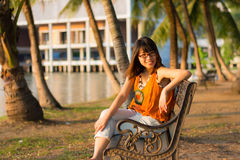 Cute Thai girl is relaxing near the riverside Stock Photos