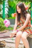 Cute Thai girl is sitting while holding pink candyfloss Royalty Free Stock Photography
