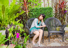 Cute Thai girl is sitting lonely on the chair Stock Image