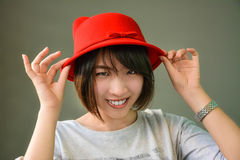 Cute Thai girl is wearing her red hat Royalty Free Stock Photography