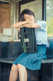 Cute Thai schoolgirl is daydreaming in an old bus stop Royalty Free Stock Photo