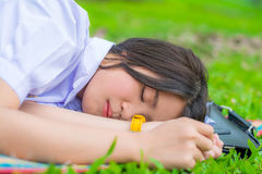 Cute Thai schoolgirl fall asleep during doing outdoor homework Royalty Free Stock Images