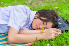 Cute Thai schoolgirl fall asleep on the mat during doing outdoor Stock Photography
