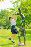 Cute Thai schoolgirl is jumping with a statue Stock Image