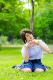 Cute Thai schoolgirl is sitting on the grass and doing heart sym Royalty Free Stock Photography