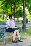 Cute Thai schoolgirl is sitting and studying on a bench Stock Photography