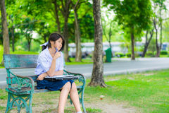 Cute Thai schoolgirl is sitting and studying on a bench Stock Photos