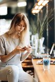A cute thin blonde girl,dressed in casual style,drinks coffee and looks at her phone in a coffee shop. royalty free stock photo