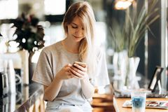 A cute thin blonde girl,dressed in casual style,drinks coffee and looks at her phone in a coffee shop. royalty free stock image