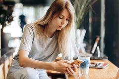 A cute thin blonde girl,dressed in casual style,drinks coffee and looks at her phone in a coffee shop. stock photography