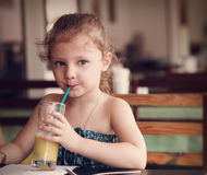 Cute thinking kid girl drinking juice in cafe with serious look Stock Images