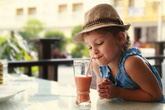 Cute thinking kid girl drinking tasty juice royalty free stock photo